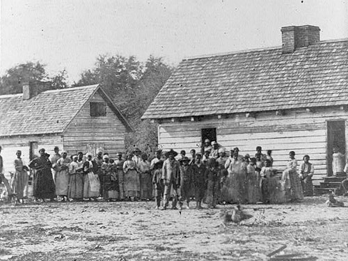 Slaves standing in front of buildings on Smith's Plantation, Beaufort, South Carolina